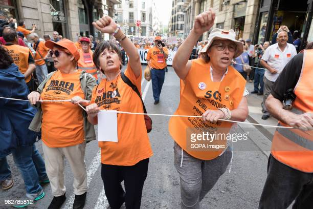 Three woman wearing orange vests rising their fist during the demonstration Hundreds or people rally in the streets of barcelona claiming for decent...