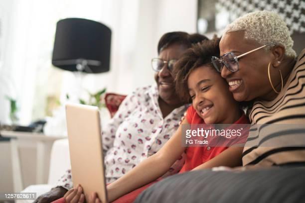 drei frauen generation familie macht einen videoanruf zu hause - mother daughter webcam stock-fotos und bilder