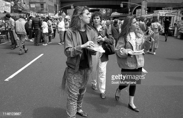 Three women all with food in their hands walk on 9th Avenue in Hell's Kitchen during the International Food Festival New York New York May 14 1988