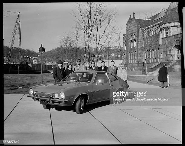 Three women and five men standing behind 1971 Ford Pinto car in between Buhl Planetarium and Allegheny Regional branch of Carnegie Library of...