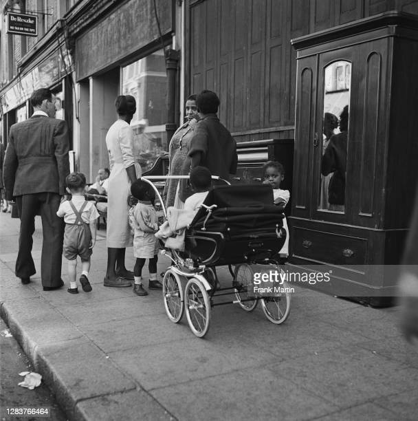 Three women and their children chatting on Portobello Road in London, circa 1958.
