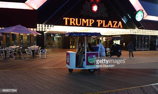 Three women are pushed down the boardwalk in a pushcart outside of Trump Plaza Casino September 15 2014 in Atlantic City New Jersey The Trump Plaza...