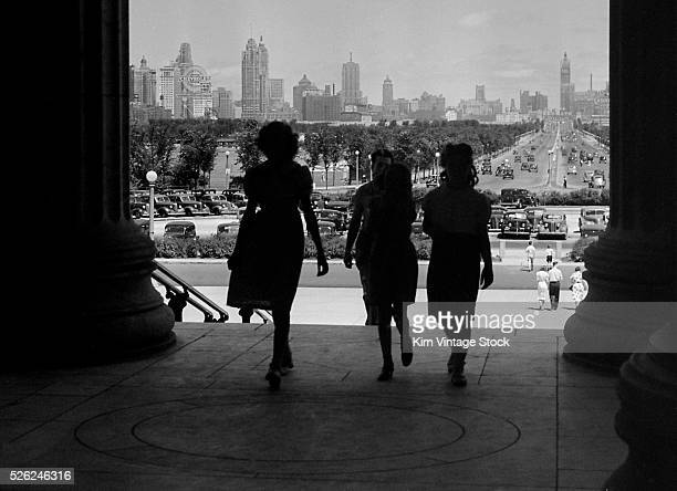 Three women are silhouetted in the shadows of the entrance to Chicago's Field Museum with a view through Grant Park to the city's skyline.