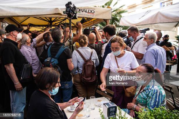 Three women at a bar table while people and journalists surround Giuseppe Conte on June 15, 2021 in Naples, Italy. The political head of the 5 Star...