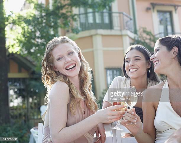 Três mulheres em um outdoor de rir e de torrar Vinho
