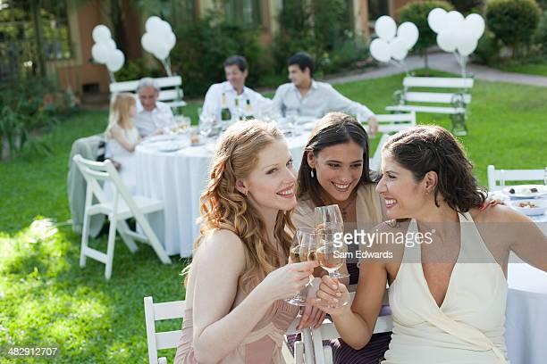 Três mulheres em uma festa ao ar livre a sorrir e Tostar