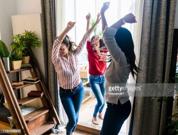 three women at home having a party and dancing - despreocupado fotografías e imágenes de stock