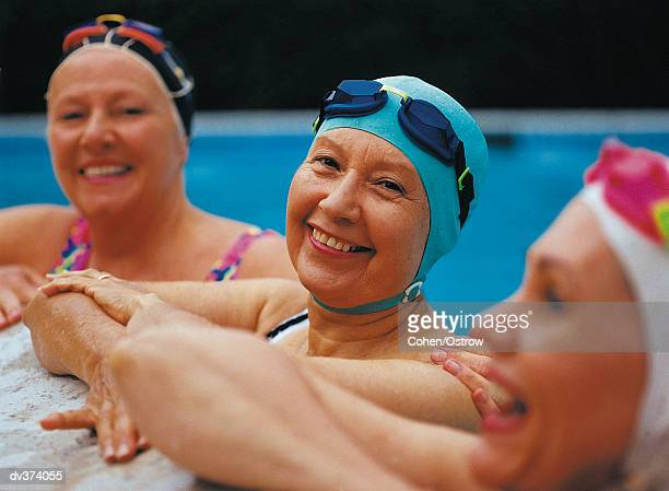 Three women at the pool's edge in caps and goggles