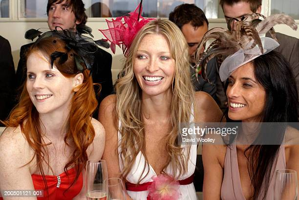 Three women at the races, smiling