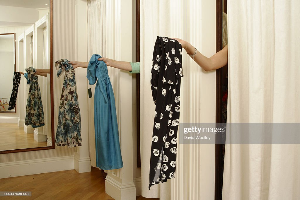 Three women behind curtains in changing room, holding out dresses : Stock Photo