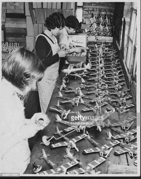 Three women build toy airplanes at a factory in East London