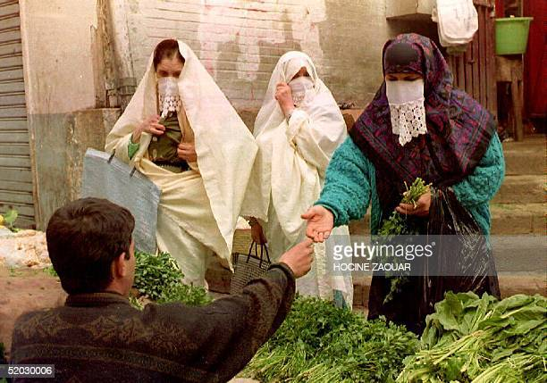 Three women buy mint for tea at an openair market 24 February 1993 on the second day of the Islamic holy month of Ramadan Curfew continued as police...