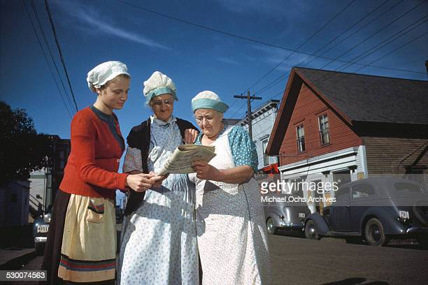 Three women cannery workers read the local paper in Lubec Maine
