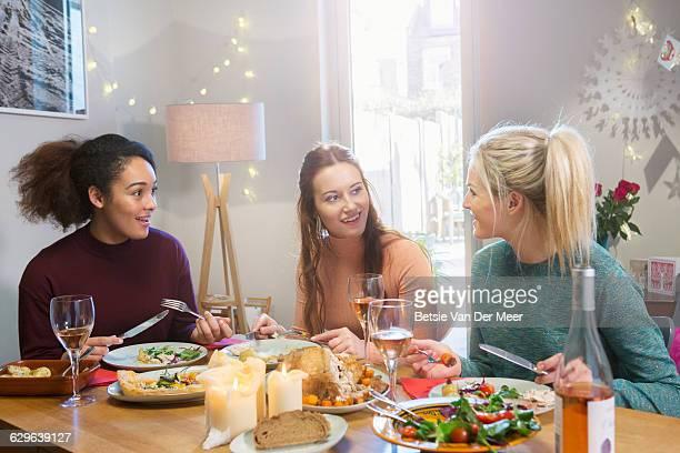 Three women chatting while having dinner.