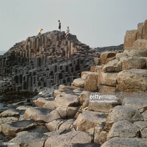 Three women clamber over basalt rock columns at the Giant's Causeway on the north coast of County Antrim near the village of Bushmills in Northern...