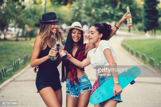 Three women clinking with beer bottles in the city park