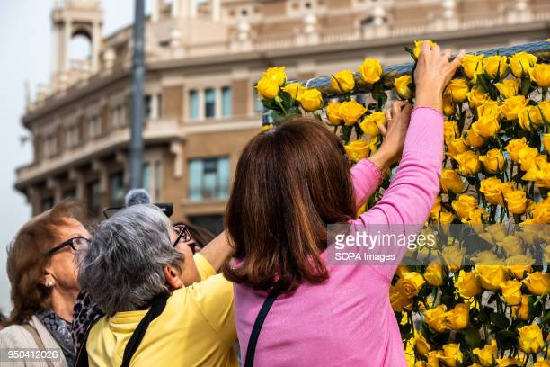 Three women deposit yellow roses on the mural of yellow roses in memory of the Catalan political prisoners Catalunya celebrates the 'Day of Sant...