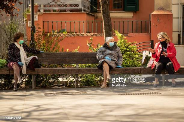 Three women discuss on a bench in the pedestrian area of Pigneto street while maintaining social distancing on April 7 2020 in Rome The Italian...