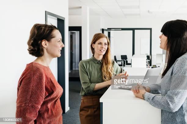 three women discussing business together in office - alleen mid volwassen vrouwen stockfoto's en -beelden