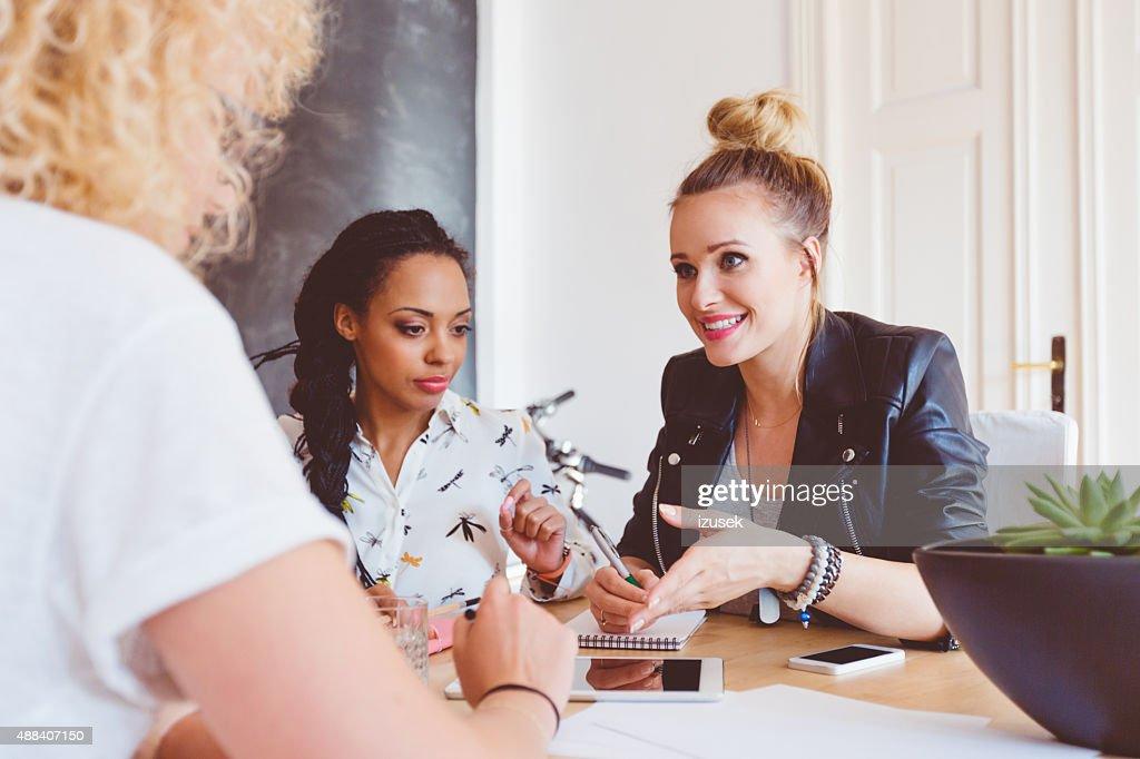 Três mulheres a discutir em um escritório : Foto de stock
