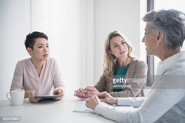 three women discussing in business meeting - mid adult women stock pictures, royalty-free photos & images