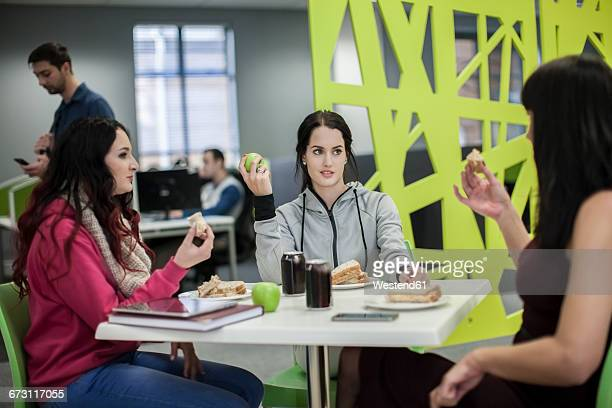 Three women discussing in office canteen