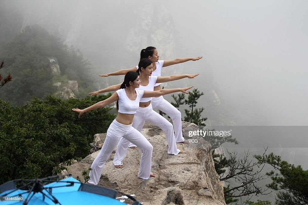 Three women do yoga on a 2,000-meter high precipice on Laojun Mountain, main peak of Funiu Mountain, during Laojun Mountain Camping Festival on July 18, 2015 in Luoyang, Henan Province of China.