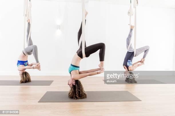 Three women doing aerial yoga exercises