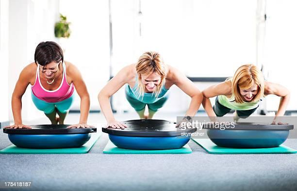 Three women doing push-ups.