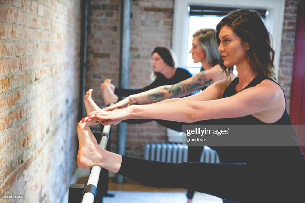 Three Women Doing Toe Stretches on a Barre : Stock Photo