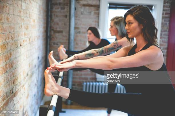 Three Women Doing Toe Stretches on a Barre