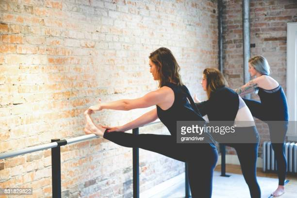 three women doing toe stretches on a barre - barre stock photos and pictures