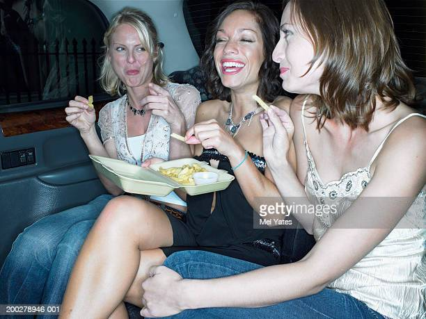 Three women eating chips in taxi, smiling