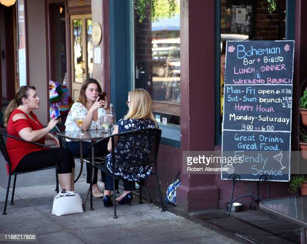 Three women enjoy drinks and conversation at a sidewalk table in front of a restaurant in Grants Pass Oregon