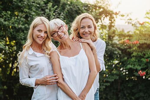 Three women enjoying outdoors, talking and laughing 1149570018