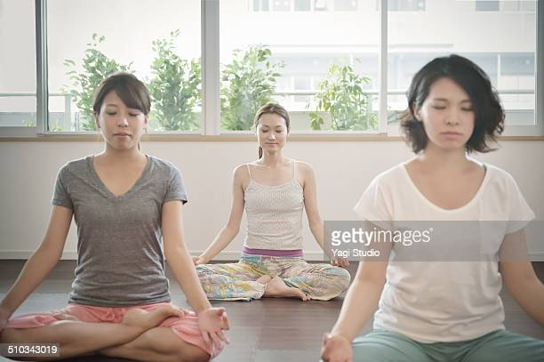 Three women enjoying yoga in room