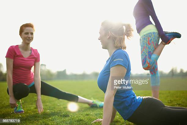 Three women exercising and stretching in the park