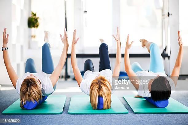 Tres la mujer el ejercicio de Pilates rodillos.