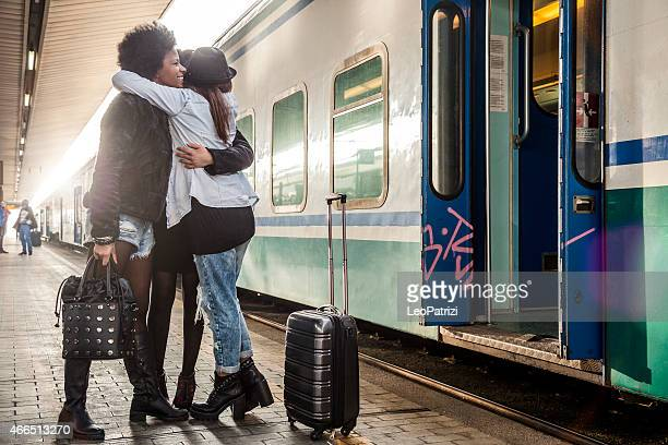 Three women friends greet at the train station
