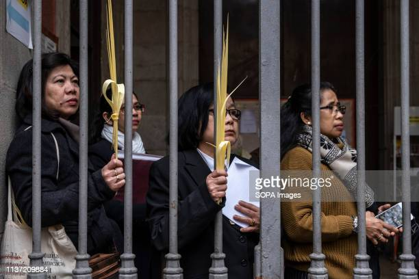 Three women from the Philippines community are seen with palms during the procession Christianity celebrates the entrance of Jesus Christ into...