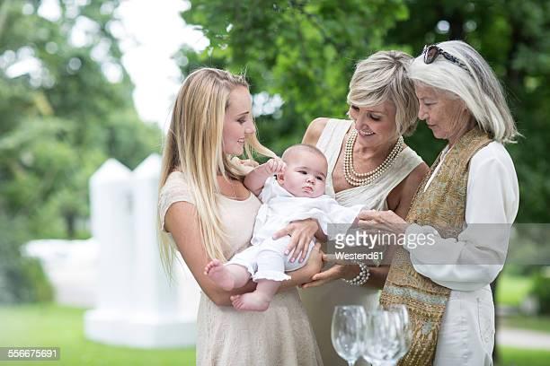 Three women gathering around baby outdoors