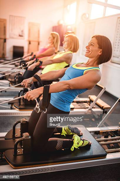 Three women having a Pilates class in a health club.
