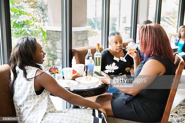 Drei Frauen, die Kaffeepause am Tisch am Fenster