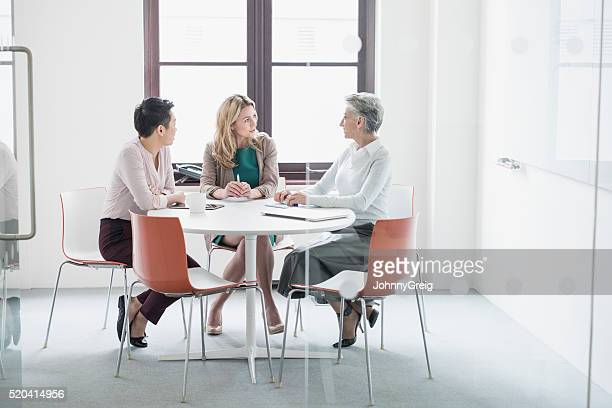 Three women having business meeting in modern office
