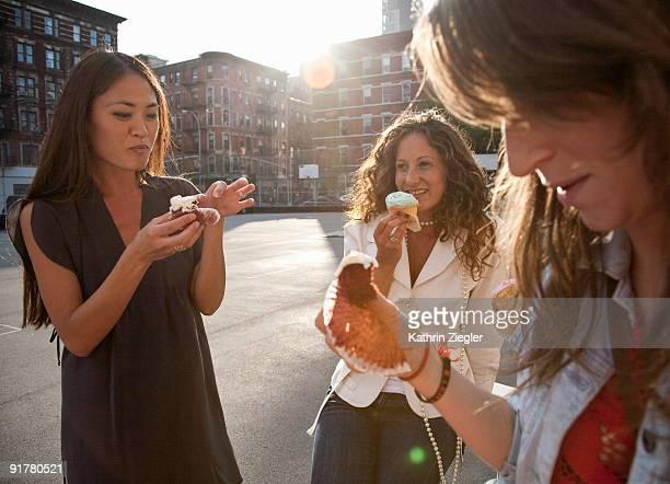 three women having cupcakes