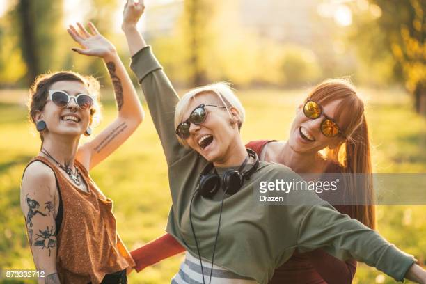 Three women having fun together in park on sunny summer day