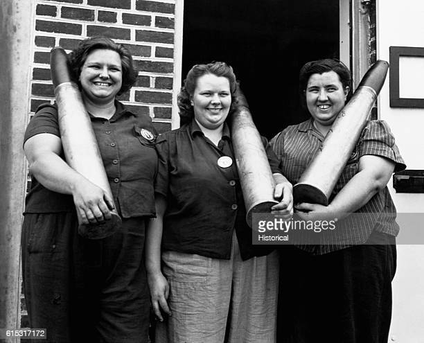 Three women hold 90mm shells at the Aberdeen Proving Grounds in Maryland