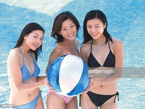 Three women holding a beach ball, smiling in the pool