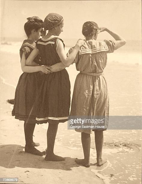Three women in bathing costumes hold each other about the waist and shoulder as they look off into the surf at the beach early 1900s