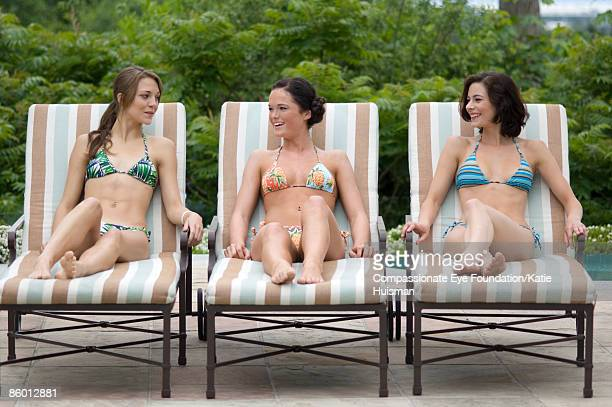 """three women in bathing suits on lounge chairs - """"compassionate eye"""" fotografías e imágenes de stock"""